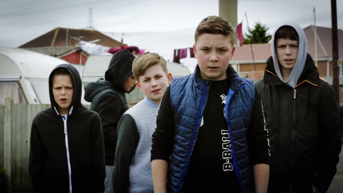 Production still from Ain't Got No Fear - a film made on the Isle of Grain with artist Mikhail Karikis in 2015-16. The image shows the stars of the film, four young teenage boys, facing the camera, with Grain Village in the background.