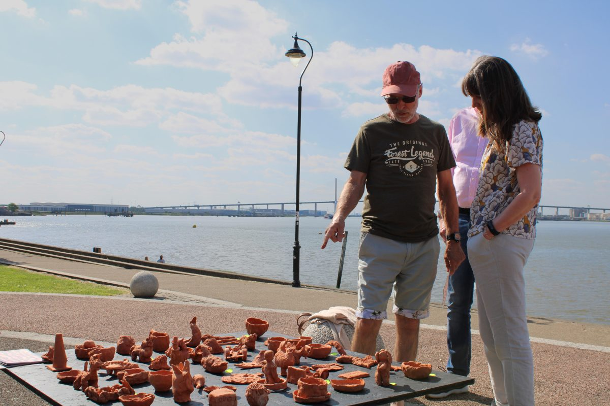 Two people stand looking at the display of ceramic objects made as part of Alison Cooke's 'Future Archaeology of Ebbsfleet', on the estuary foreshore at Greenhithe, adjacent to the site where the clay was dug.