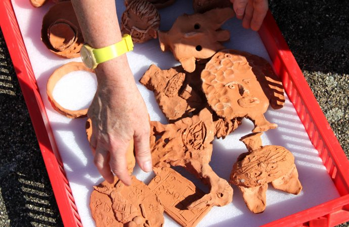 A hand picks up the ceramic objects, made as part of Alison Cooke's 'Future Archaeology of Ebbsfleet', from a red crate lined with padding..