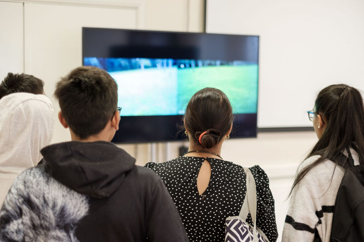 A group of five people stand looking at a large screen, watching a video made by artist Shepherd Manyika.