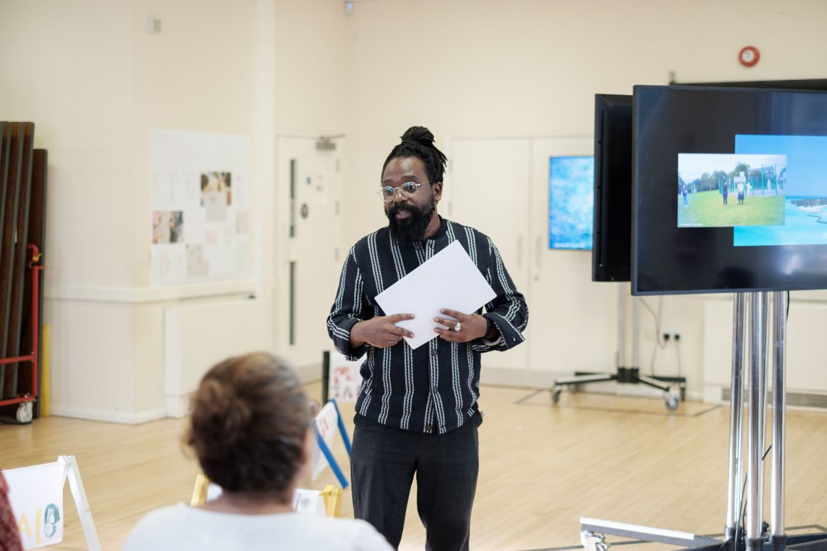 In a town hall artist Shepherd Manyika stands speaking to a group of people, in front of several screens displaying videos and artworks on paper displayed on low wooden frames.